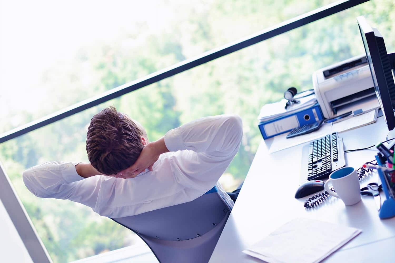 Geschäftsmann lehnt sich entspannt zurück in seinem Büro